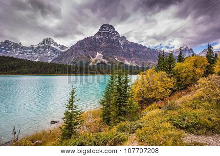 Autumn Bow River in Banff National Park, Canada. Azure waters of the river are surrounded with Rocky Mountains and magnificent yellow and orange vegetation