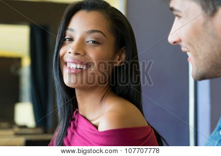 Closeup shot of young african woman smiling. Happy black girl laughing and looking at camera. Carefree girl in casual looking at camera with positivity and vitality.