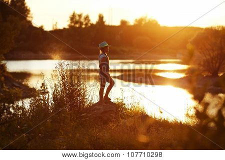 Girl In Hat Stands On The River Bank At Sunset