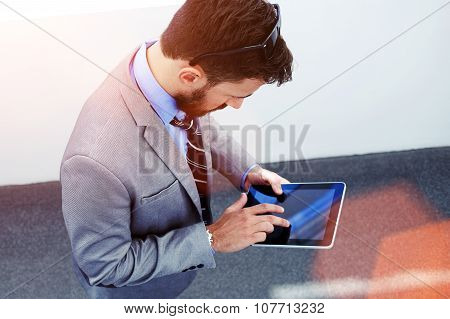 Skilled male dressed in luxury suit working on digital tablet before meeting