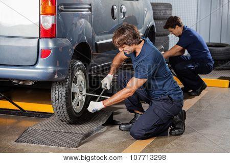 Male mechanics fixing car tires at auto repair shop