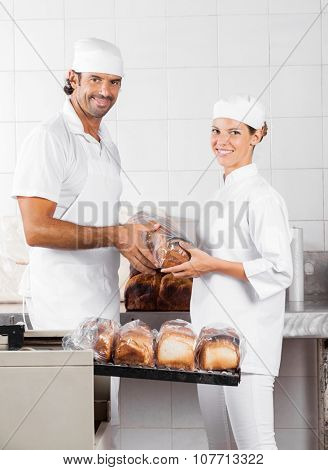 Portrait of smiling male and female Baker's packing bread loaves in bakery