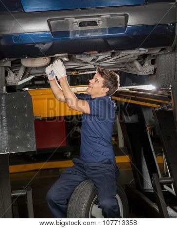Young male mechanic repairing underneath lifted car at auto repair shop