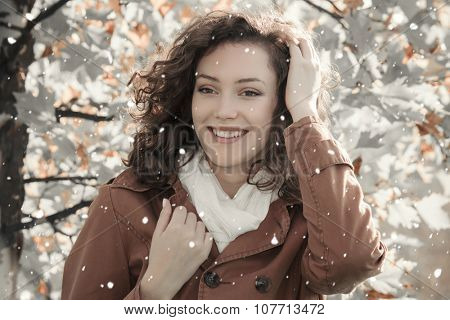 Outdoors portrait of a young beautiful smiling woman with falling snow