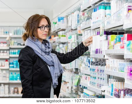 Mid adult female purchaser choosing product in pharmacy