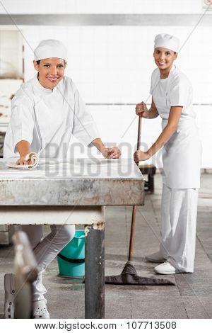 Portrait of happy female Baker's in uniform cleaning bakery