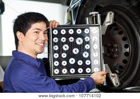Happy mechanic looking away while adjusting aligner on car wheel in garage