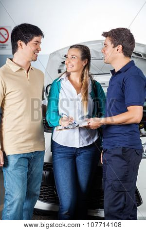 Male mechanic taking sign on invoice from happy couple in garage