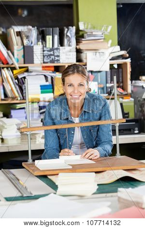 Portrait of happy mid adult woman binding papers at workbench in factory
