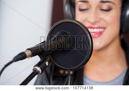 Closeup of mike and condenser with young woman singing in recording studio