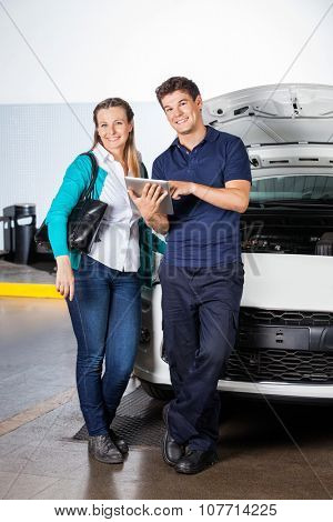 Portrait of happy female customer and mechanic with digital tablet standing by car in garage