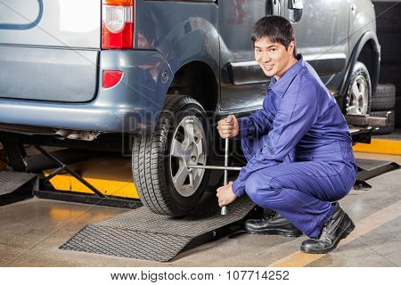 Portrait of happy mechanic fixing car tire with rim wrench at garage