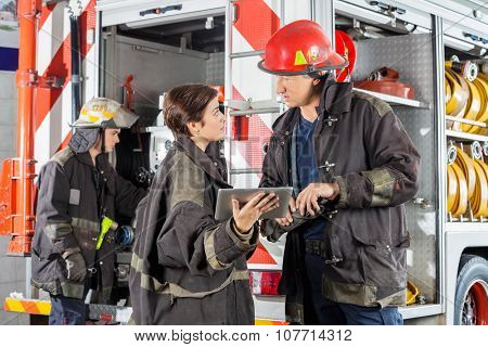 Male and female firefighters discussing over digital tablet against truck at fire station