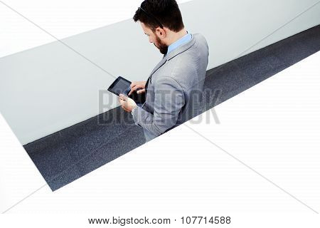 Confident businessman in formal wear using digital tablet in office interior