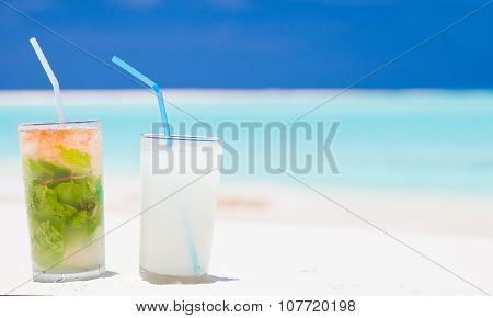 exotic mojito and pina colada cocktails on white sand beach