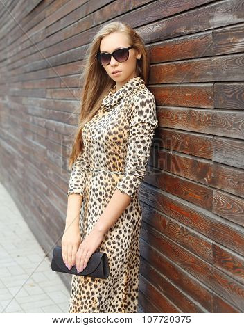 Beautiful Woman Wearing A Leopard Dress And Sunglasses With Handbag Clutch In The City