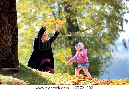 The woman with the girl collect leaves of trees in park