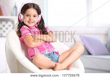Attractive little girl sitting on comfortable chair and listening music with pink headphones in the room