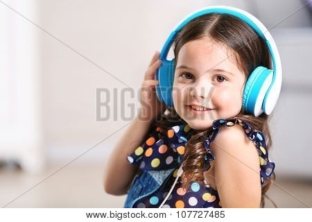 Pretty smiling little girl listening music in light room