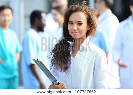 Attractive young woman doctor with clipboard in hands against group of medics