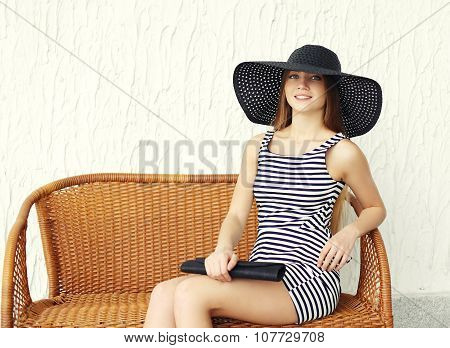 Beautiful Young Woman Wearing A Striped Dress, Black Straw Hat And Handbag Clutch Sitting On Chair