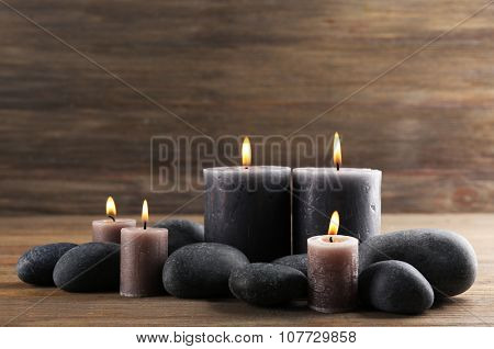Alight wax grey candle with pebbles around on wooden background