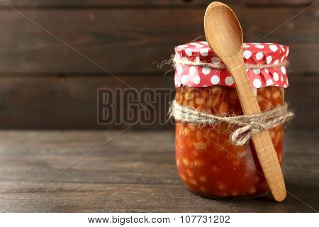 Glass jar of preserved beans and wooden spoon, on wooden background