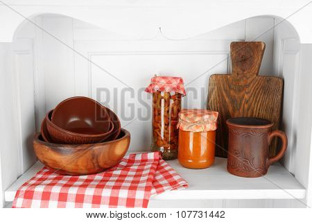 Jars with pickled vegetables and kitchenware on shelf