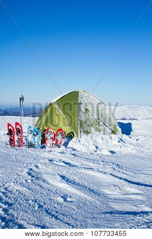 Tent winter mountains.Tent stands in the mountains in the snow. Snowshoes are beside the tent.