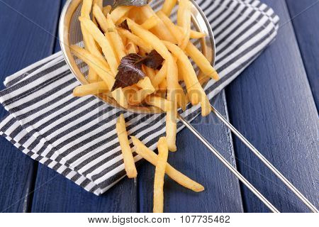 French fried potatoes in metal colander with sauce on wooden background