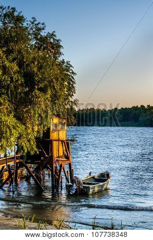 Old Dock And The Boat On The Lake. Rustic Landscape With Wooden Pier In The Summer Sunset.