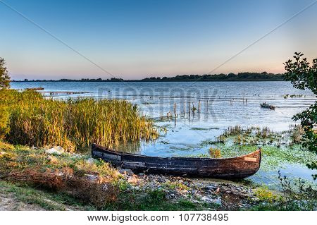 Old Boat On The Water In The Lake Among The Reeds. Bright And Calm View With Wooden Boat On The Coas