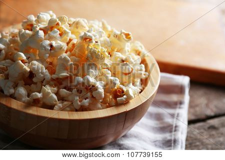 Salted popcorn in a bowl on stripped napkin with board and glass of corns on wooden table