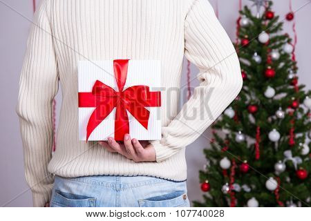 Christmas Concept - Man Hiding Gift Box Behind Back