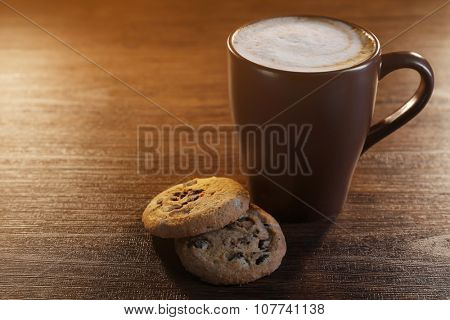 Cup of coffee with milk foam and  cookies with chocolate crumbs on wooden background