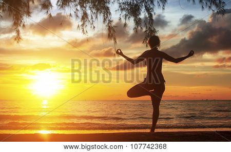 Young woman practicing yoga at sunset on the Ocean coast.