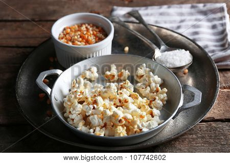 Salted popcorn in a metal bowl with cup of corns on wooden table