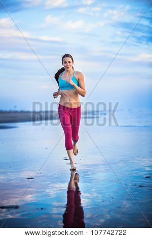 Woman running through water on the beach at sunset