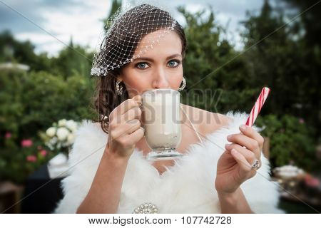 Beautiful bride drinking hot chocolate and holding a peppermint stick