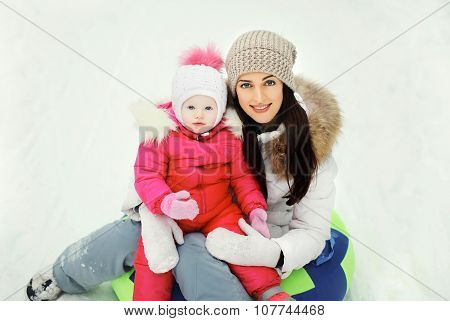 Happy Mother And Child Sitting Together On Sled In Winter Day