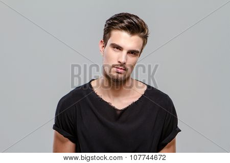 Portrait of indifferent young handsome man in black t-shirt