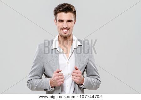 Portrait of young happy successful businessman in gray jacket and white shirt