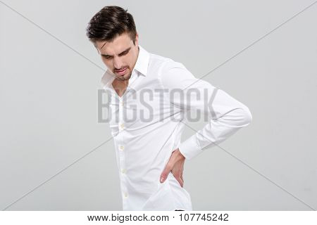 Handsome attractive young man in white shirt has a backache