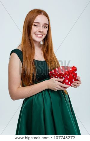 Portrait of a happy redhair woman in dress holding gift box isolated on a white background