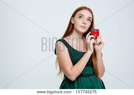 Portrait of a young redhair woman holding jewelry box and dreaming isolated on a white background