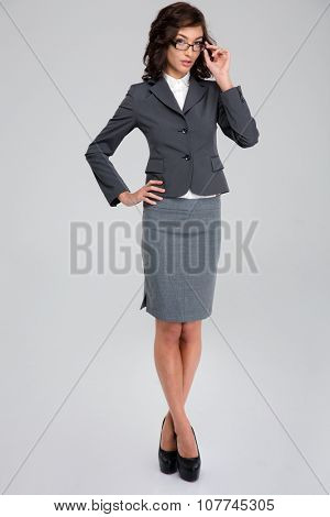 Concentrated confident curly pretty business woman in glasses and gray suit standing crossing legs and touching her glasses