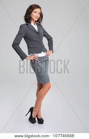 Full length portrait of young beautiful curly happy woman posing in formalwear