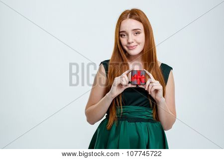 Portrait of a happy redhair woman holding jewelry box isolated on a white background and looking at camera