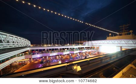 People Enjoy Night Party On The Deck Of Illuminated Cruise Ship