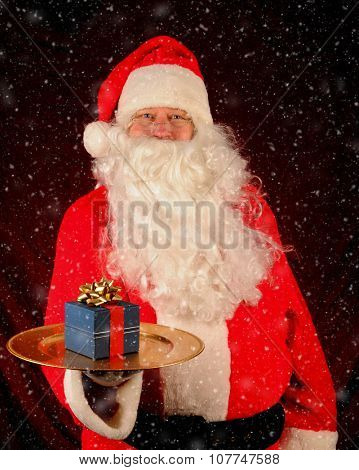 Santa Claus holding a serving tray with a wrapped present with a snow effect added. Vertical format